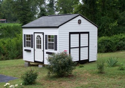 A 12x12 vinyl shed with an a-roof style shingle roof. Shed has a circle top house door with two windows on either side. The shed has a double door on gable end