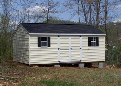 A 12x20 vinyl shed with an a-roof style roof. The shed has a set of double doors and two windows with black shutters. Shed has a 10 foot ridge vent