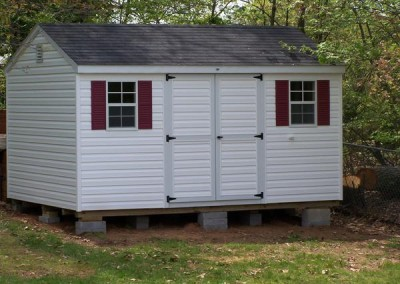 A 10x14 vinyl shed with a shingled, a-roof style roof and a set of double doors with windows on either side