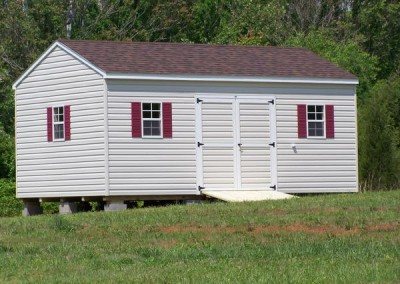 A vinyl shed with a shingled, a-roof style roof. The shed has a set of double doors and three windows with shutters