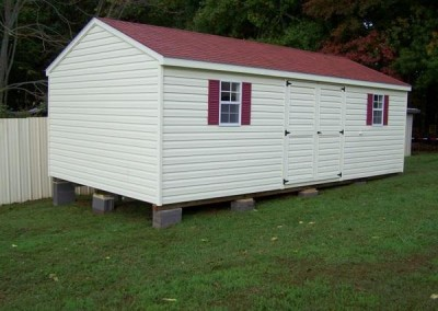 12 x 24 V-A-roof with tile red blend shingles, cream siding and trim, and maroon shutters
