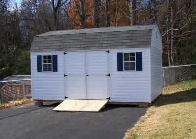 12 x 16 V-High Barn with white siding and trim, estate gray shingles and bedford blue shutters with a treated wooden ramp.