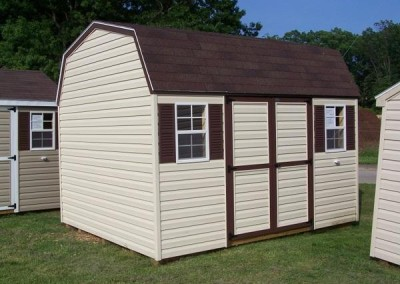 A 10x12, vinyl shed with a barn style roof. Shed has two windows and a set of double doors.