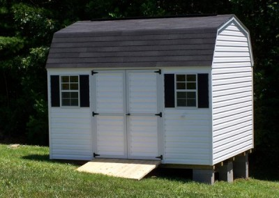 A 10x12 white vinyl shed with a shingled, barn style roof. Shed has a set of double doors and two windows with a treated wooden ramp