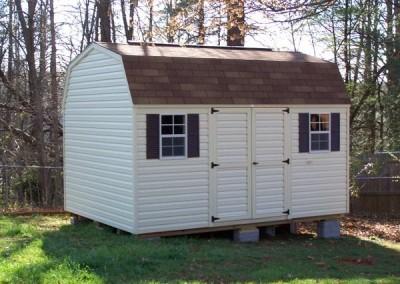 10 x 14 V-High Barn with cream siding and trim, desert tan shingles and dark brown shutters