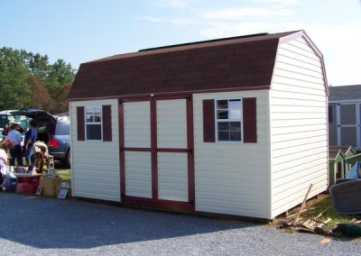 A white vinyl shed with a shingled, barn style roof. Shed has two windows with shutters and solid, vinyl double door