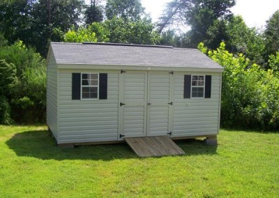 A vinyl, 10x16 shed with an a-roof style, shingle roof. Shed has double door, two windows, and a wooden ramp