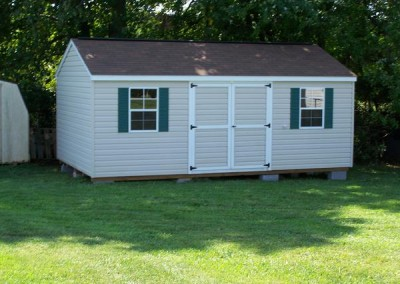 A white vinyl shed with a double door and two windows with green shutters. Shed has a shingled, a-roof style roof