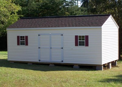 A vinyl 12x12 shed with an a-roof style shingled roof. Shed has a solid double vinyl door and two windows with maroon shutters.