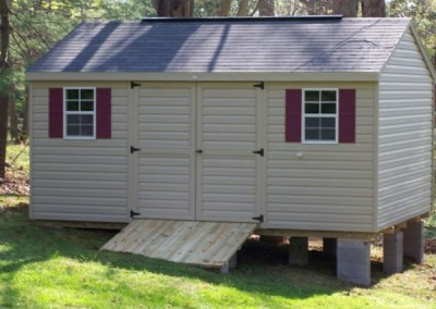 12 x 16 V-A-roof with tan siding and trim, estate gray shingles and maroon shutters and treated wooden ramp