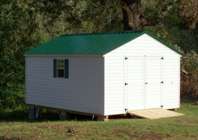 12 x 16 V-A-roof with white siding and trim, green metal roof, and green shutters and treated wooden ramp
