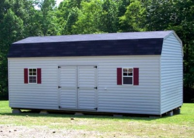 12 x 24 V-High Barn with gray siding, gray trim black shingles, maroon shutters and 1' taller walls