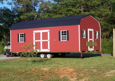 A red vinyl, 14x28 size shed with a black metal, barn style roof. Shed has two large windows and a set of double doors along one side. On gable end, the shed has a 3 foot vinyl door and two smaller windows on either side. Shed is loaded on a trailer for transport.
