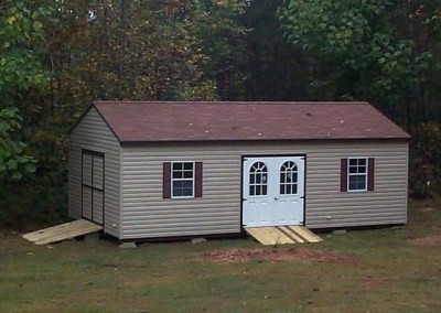 A 14x28 sized vinyl shed with an a-roof style roof. Shed has a double door on gable end with a treated wooden ramp. Shed side has two windows on either side of a double circle top house door with a treated wooden ramp
