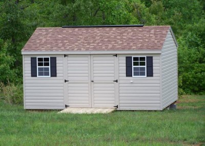 12 x 16 V-A-roof with tan siding and trim, resawn shake shingles, redwood shutters and a ridgevent