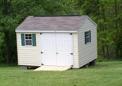 10 x 12 V-A-roof with cream siding, white trim, driftwood shingles, green shutters, fiber doors and a ridgevent