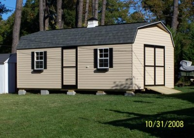 A vinyl high barn with a shingled, barn style roof. Shed has a 3 foot wide vinyl door and two windows on side. A set of double doors with a wooden ramp are on the gable end. Shed has a cupola on roof