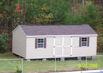 A vinyl shed with a a-roof style shingled roof. Shed has double doors, two windows with shutters and a ridge vent