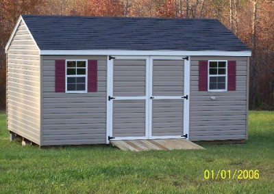 A vinyl shed with white trim and an a-roof style, shingled roof. Shed has maroon shutters and a treated wooden ramp