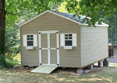 A vinyl 12x20 shed with a 4 foot wide double door. Shed has tow windows on either side of door and a treated wooden ramp