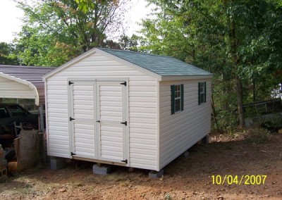 A vinyl shed with 2 windows and a set of double doors. The roof is an a-roof style and is shingled. The shed has two windows and two shutters.