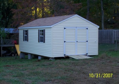 A 12x20 vinyl shed with an a-roof style, shingled roof. Shed has a vinyl double door on gable end with a treated wooden ramp and two windows along shed side