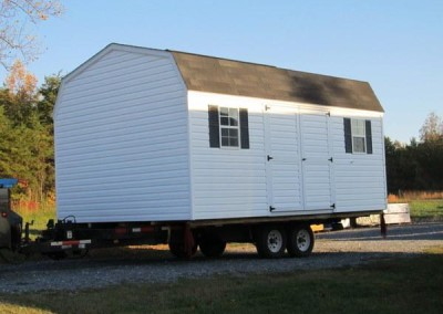 A white vinyl 12x28 size shed. Shed has black, supreme shingles, and a barn style roof. Shed has a set of double doors and two windows with shutters. Shed is loaded on a trailer for transport