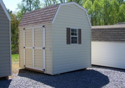 A 8x8 vinyl shed with a shingled barn style roof. Shed has a vinyl double door and a window with shutters