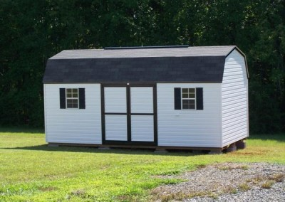 A 10x20 white vinyl shed with a shingled, barn style roof. Shed has a ridge vent, a solid vinyl double door and two windows with shutters