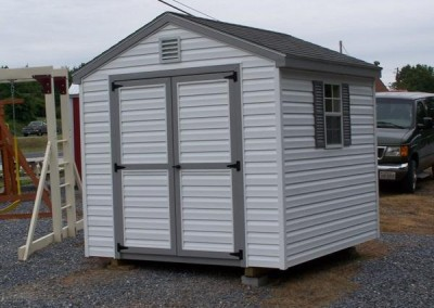 An 8x8 white vinyl shed, with a double door and two windows with shutters and a 8x8 white gable vent. Shed has a shingled a-roof style roof
