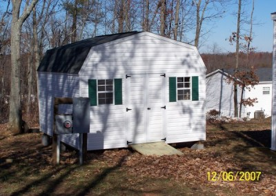 A white vinyl shed with a set of 4 foot wide double doors. Shed has two windows and a wooden ramp. The roof is a barn style and is shingled.